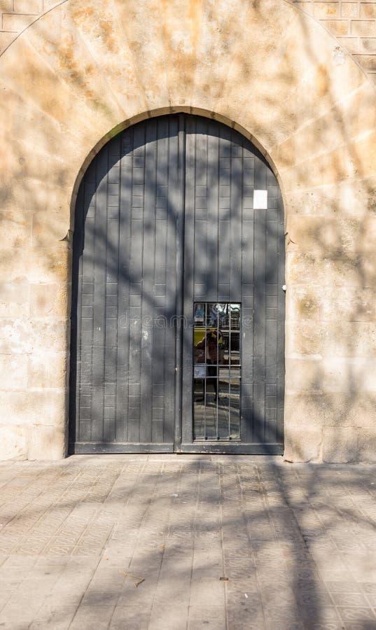 BARCELONA, SPANIEN - 24. FEBRUAR 2019: Alte h?lzerne graue Einstiegst?r mit der Reflexion des Fotografen im T?rfenster herein lizenzfreies stockbild