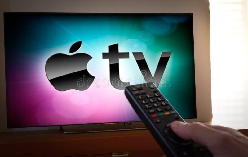 Barcelona, Spanien Januar 2019: Mann hält eine Fernbedienung mit dem Apple Fernsehikonenschirm im Fernsehen lizenzfreie stockfotos