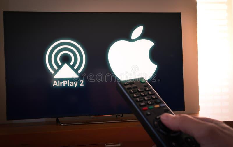 Barcelona, Spanien Januar 2019: Mann hält eine Fernbedienung mit dem Apple und Schirm der Ikone Airplay2 im Fernsehen lizenzfreies stockfoto