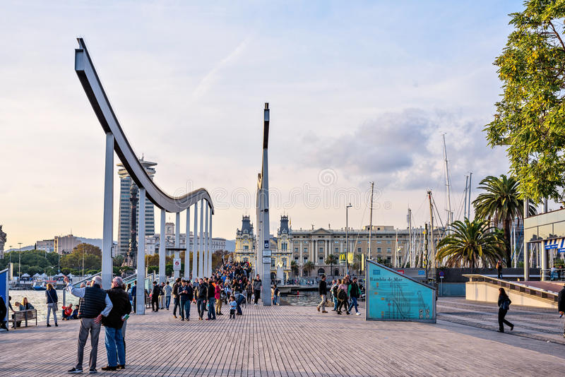 Barcelona Spanien: November 13, 2016: Rambla Del Mar trägångbana över port Vell på solnedgången royaltyfri fotografi