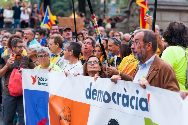 Barcelona Spanien - 1 oktober 2018: kvinnan ser upp på det hållande demokratibanret för den catalan flaggan under protesten för c royaltyfri bild