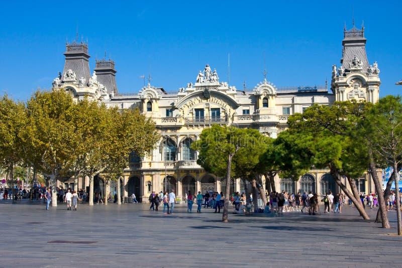 BARCELONA SPANIEN - OKTOBER 18, 2014: Turister nära gammal byggnad för Barcelona portmyndighet, port de Barcelona, på grunden av  fotografering för bildbyråer