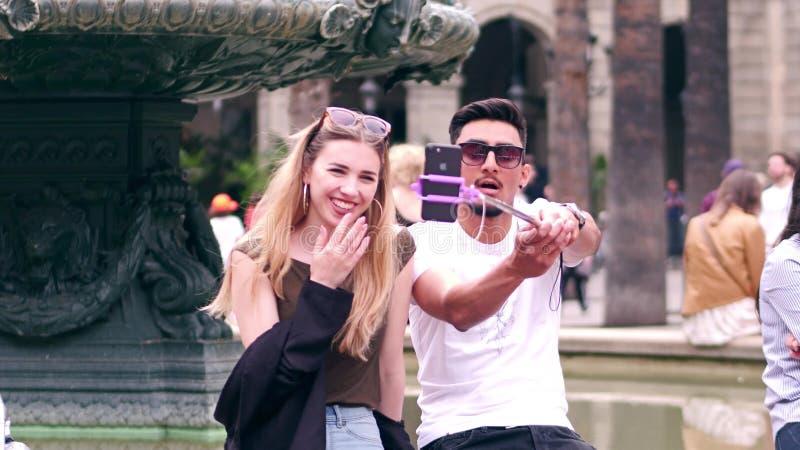 BARCELONA, SPANJE - APRIL, 16, 2017 Mooi jong paar die tussen verschillende rassen selfies met een mobiele telefoon en een staaf  stock foto