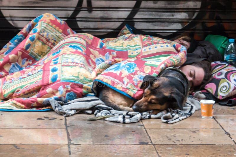 BARCELONA, SPANJE, 4 Februari, de jonge dakloze kerel van 2018 A, een meisje stock afbeeldingen