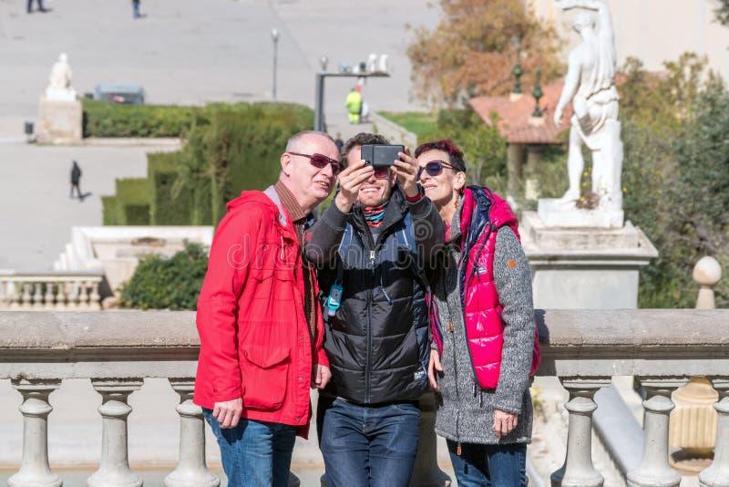 Barcelona, Spanje - Maart 12, 2019: Een groep toeristen die selfies gebruikend een smartphone doen stock fotografie