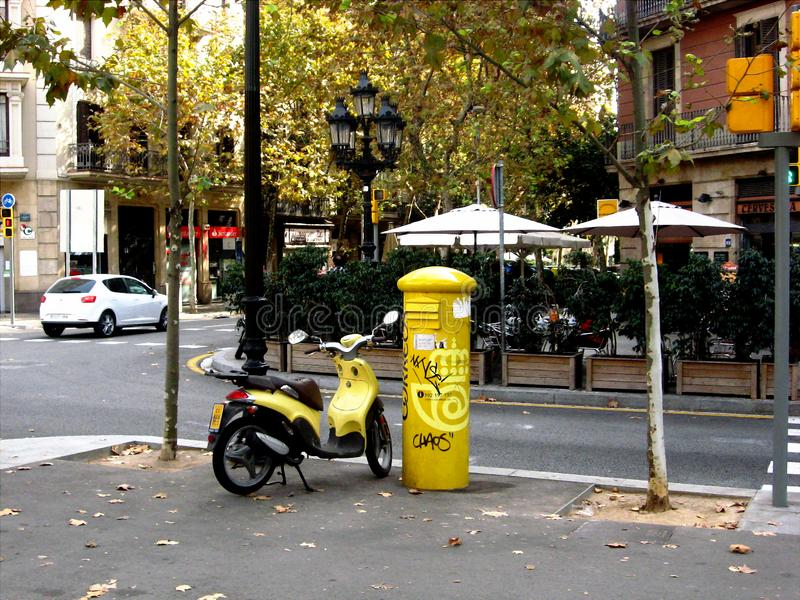 Barcelona, street corner with yellow scooter and restaurant terrace royalty free stock images