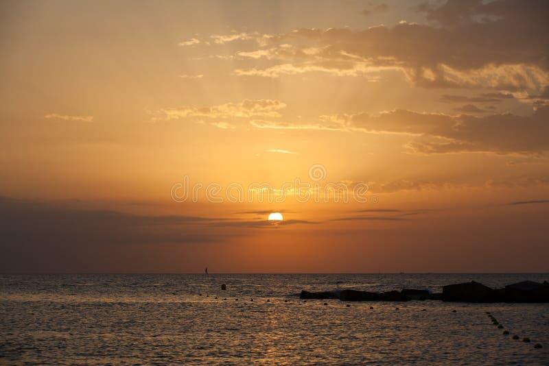 Barcelona sunrise with yacht on horizont. Barcelona sunrise on sea with sport yacht on horizont royalty free stock images