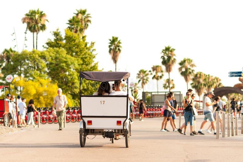 Barcelone, Espagne - 7 juillet 2019 : touristes dans le pousse-pousse de cycle au coucher du soleil dans le vieux port de ville a photo stock