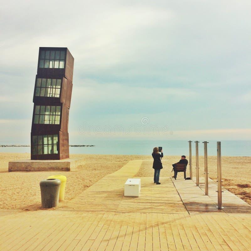 Barceloneta, Barcelona, February 2017: people observe beach. Barceloneta, Barcelona, February 2017: people observe sandy beach . Monument on a beach royalty free stock photography