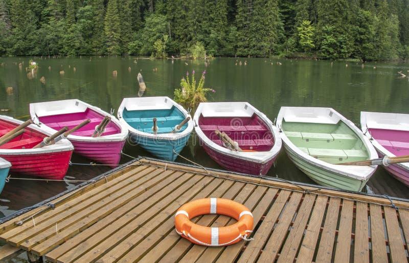 Barche colorate nel lago rosso in Romania fotografia stock libera da diritti