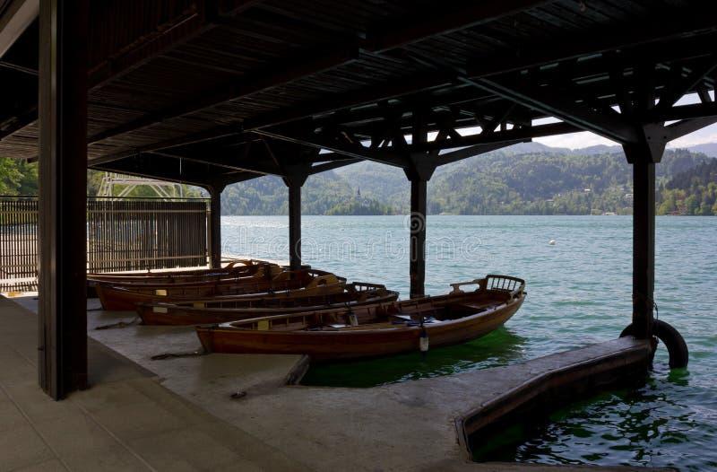 Barche di legno nel lago sanguinato fotografia stock