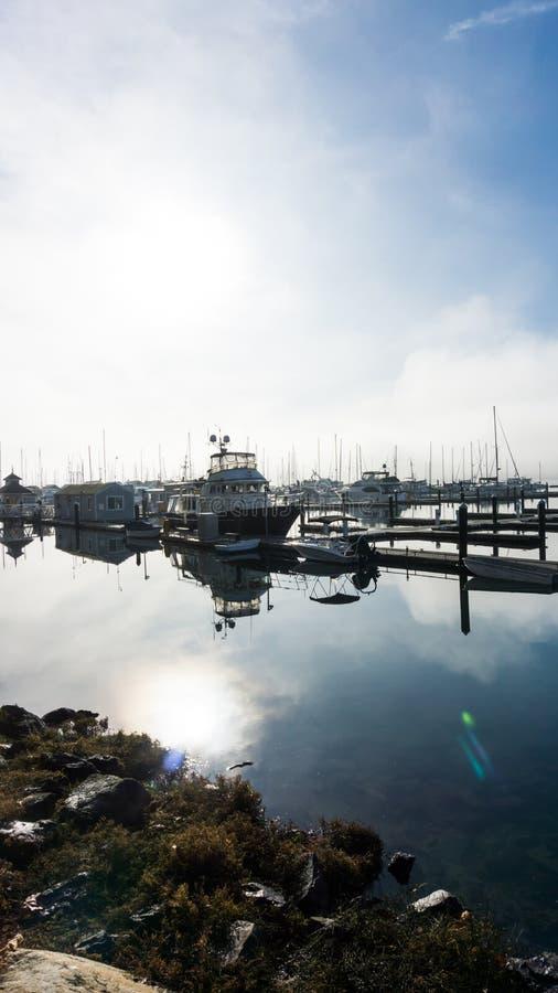 Barche messe in bacino su una mattina nebbiosa fotografie stock