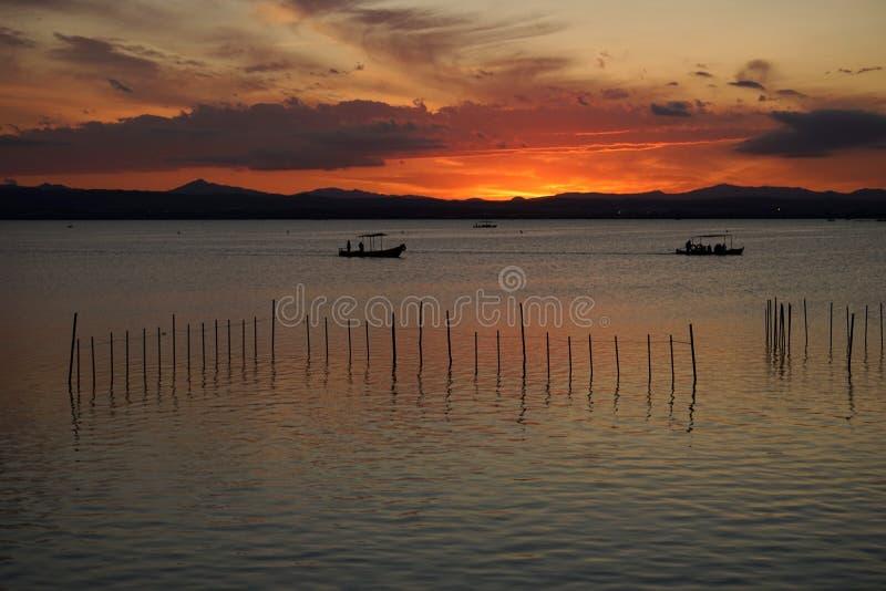 Barche nell'ambito del tramonto fotografia stock