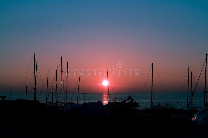 Barche profilate in un porto al tramonto fotografia stock libera da diritti