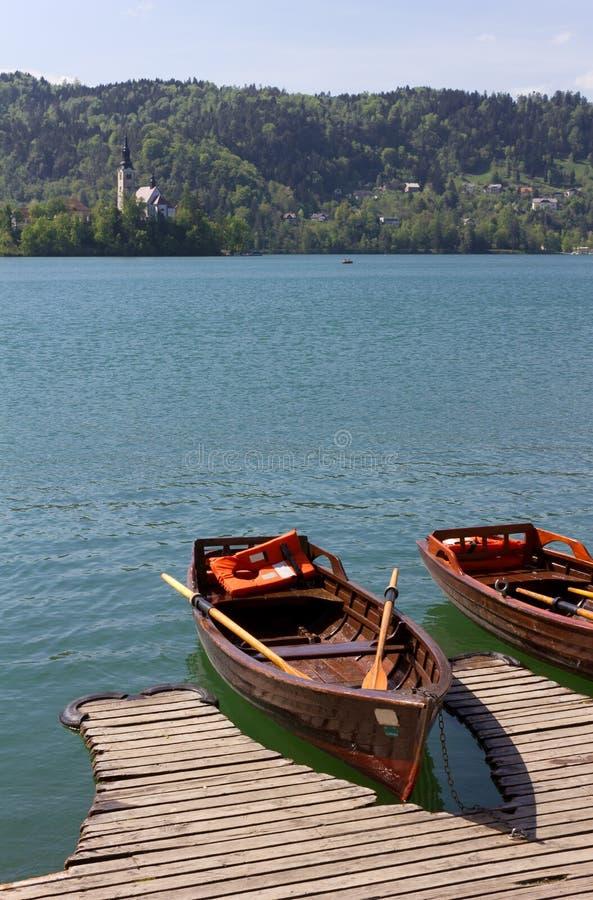 Barche a remi di legno nel lago sanguinato immagini stock libere da diritti
