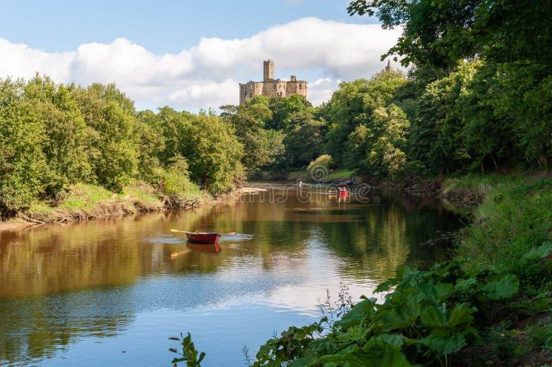 Barche a remi sul fiume Coquet con il castello di Warkworth in sottofondo immagine stock