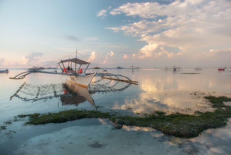 Barche su una spiaggia tropicale ad alba fotografie stock libere da diritti