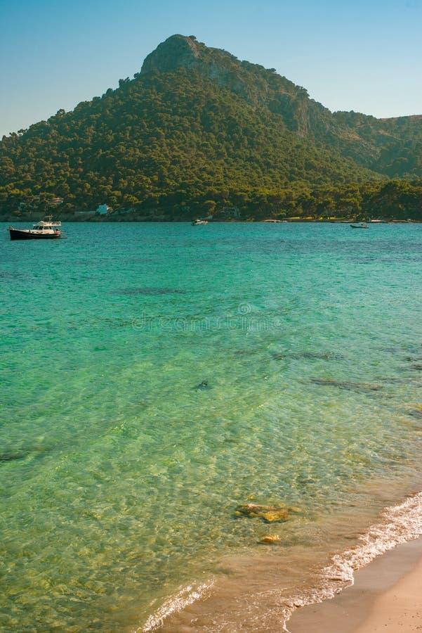 Barche sul mare del turchese e sulla spiaggia di sabbia bianca con la collina fertile nei precedenti fotografia stock libera da diritti