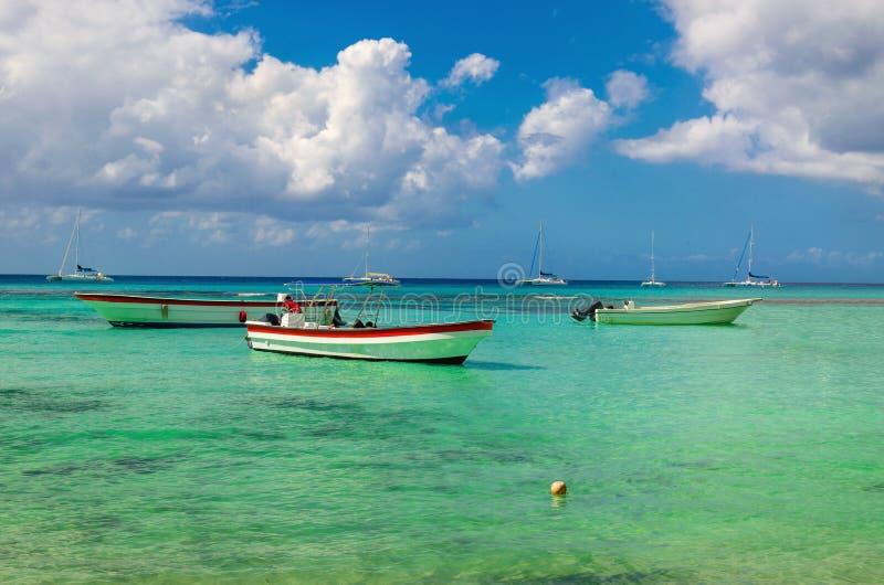 Barche variopinte di legno sulla chiara acqua azzurrata del mar dei Caraibi su un fondo di cielo blu con le nuvole bianche fotografie stock libere da diritti