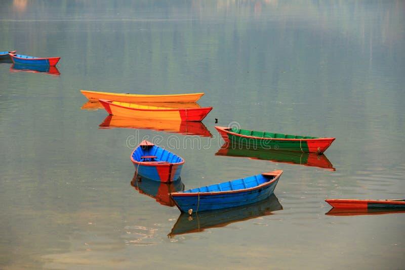 Barche variopinte e le loro riflessioni sul lago di phewa fotografia stock libera da diritti