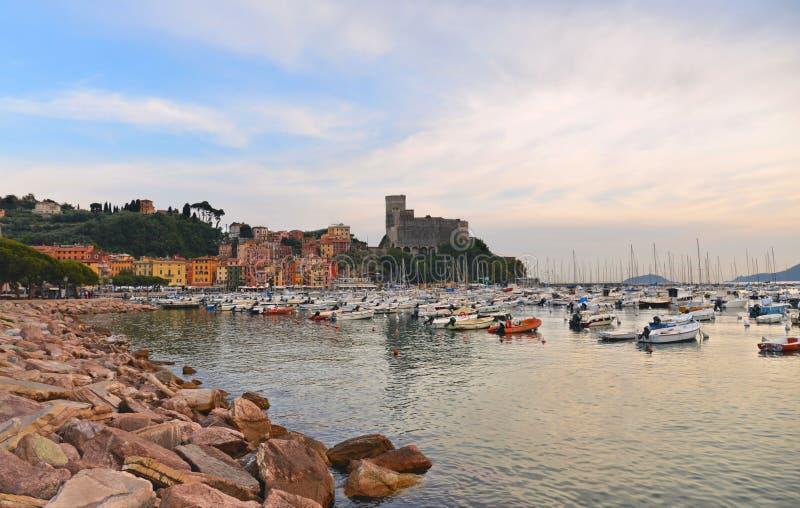 Barche variopinte e vista sul mare con il vecchio castello ed il cielo nuvoloso blu con il tramonto in Lerici in Liguria, Italia immagine stock