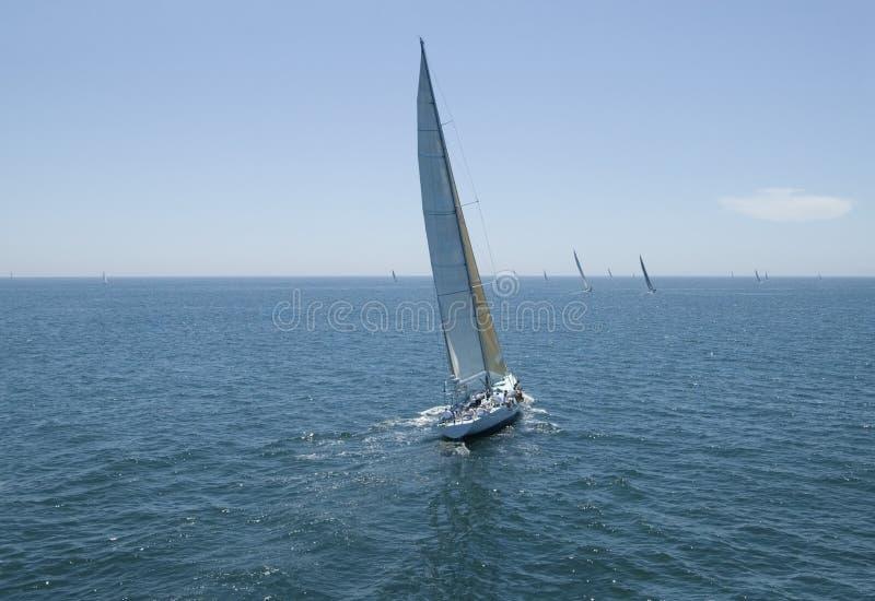 Barche a vela che corrono nell'oceano blu contro il cielo fotografia stock