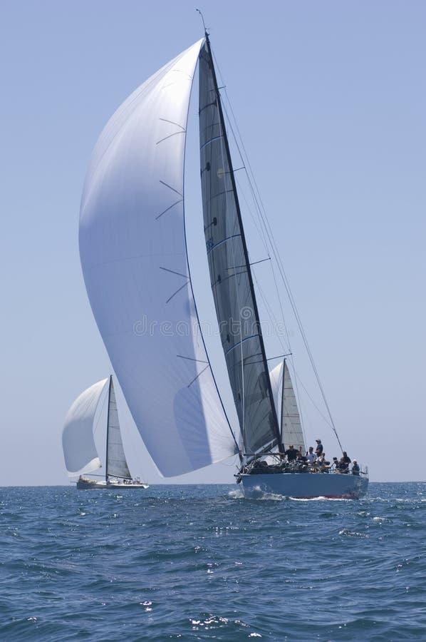 Barche a vela che corrono nell'oceano blu contro il cielo immagine stock