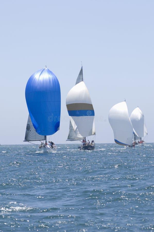Barche a vela che corrono nell'oceano blu contro il cielo fotografia stock libera da diritti