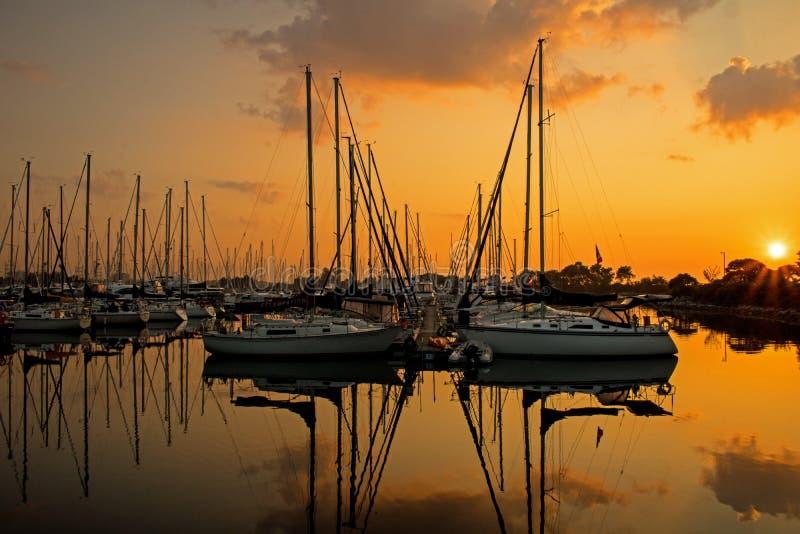 Barche a vela che creano vicino alla simmetria all'alba fotografia stock libera da diritti