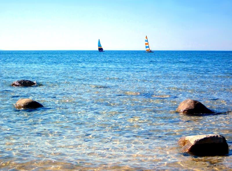 Barche a vela in chiara acqua blu con cielo blu fotografie stock