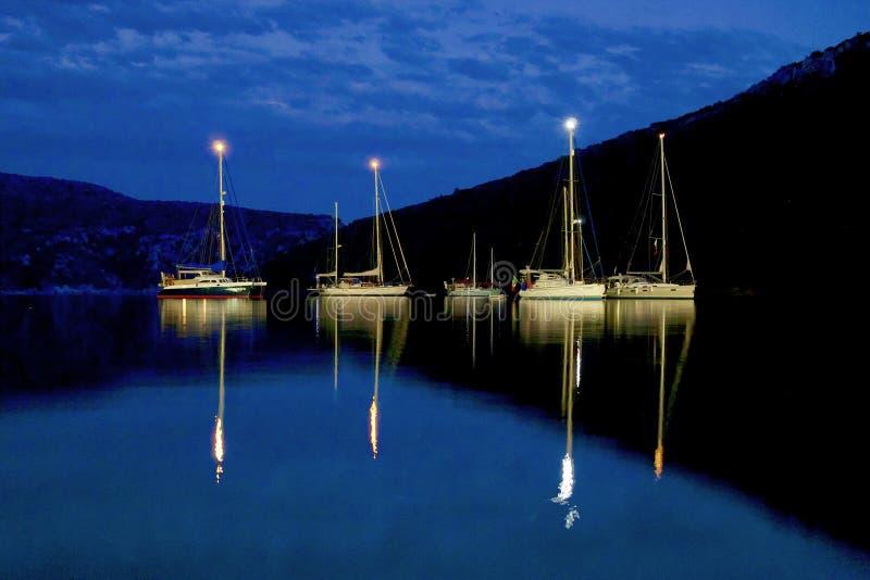 Barche a vela illuminate dalla luna sul mare alla notte fotografia stock libera da diritti