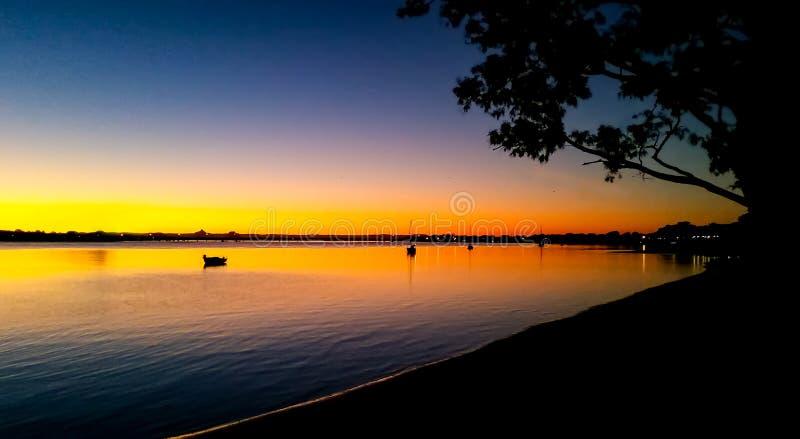 Barche a vela nel tramonto - vista verso il ponte dell'isola di Bribie sopra il passaggio della pietra pomice con le montagne del fotografia stock libera da diritti