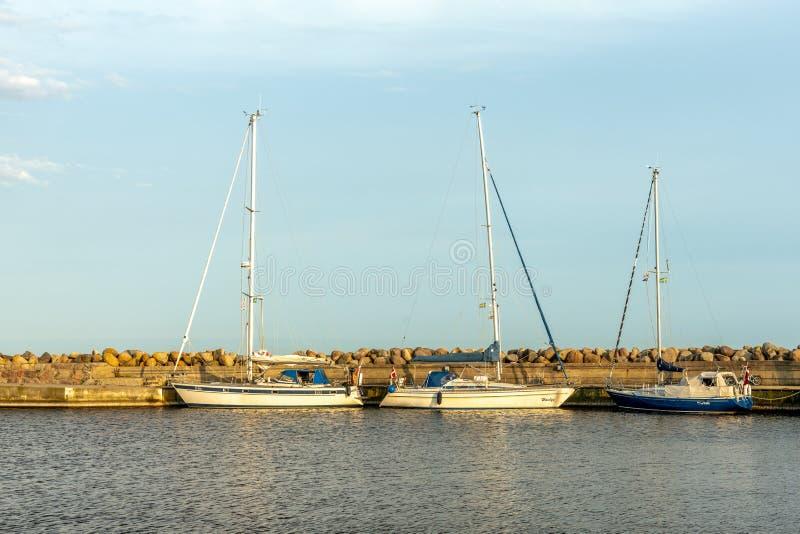 Barche a vela ormeggiate al molo alla luce del sole della sera gialla fotografia stock