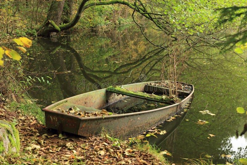 Barco abandonado en la charca del bosque fotos de archivo