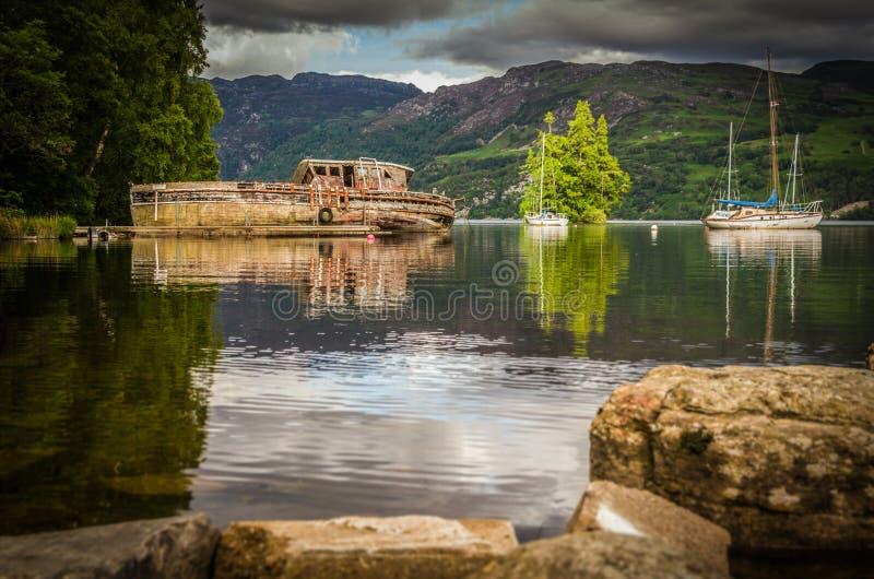 Barco abandonado velho no lago rippling de Loch Ness foto de stock royalty free