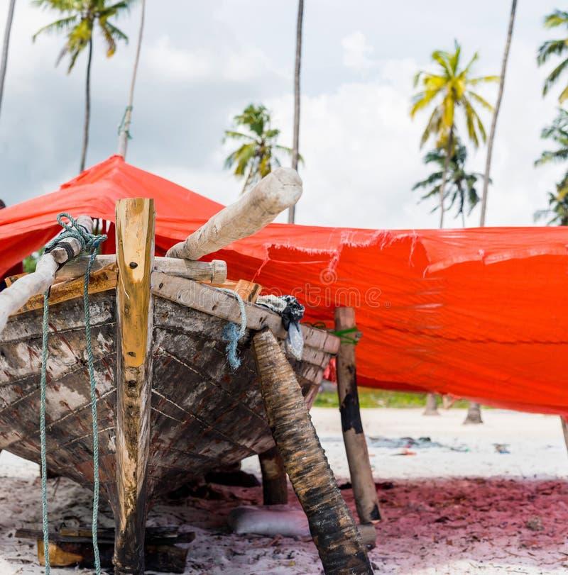 Barco africano de madera en una orilla cubierta con la lona roja imagen de archivo libre de regalías