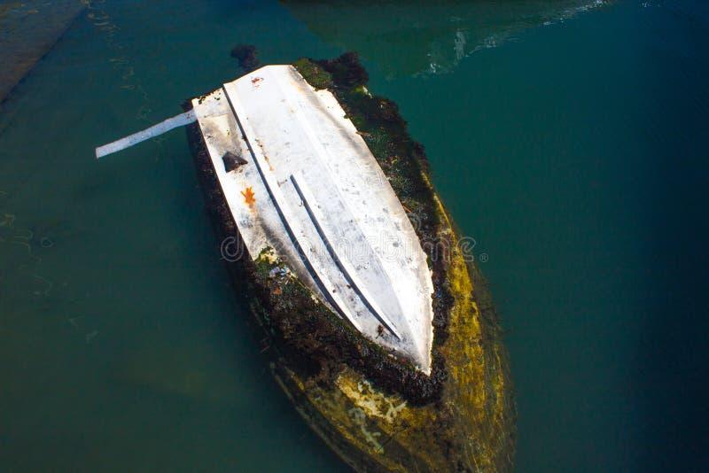 Barco afundado no porto em um mar imagens de stock royalty free