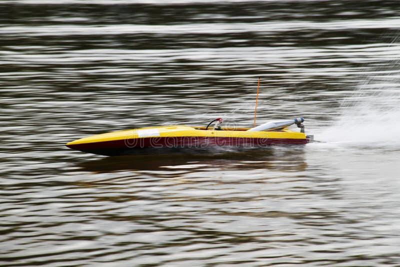 Barco amarelo de RC que apressa-se em um lago fotos de stock royalty free
