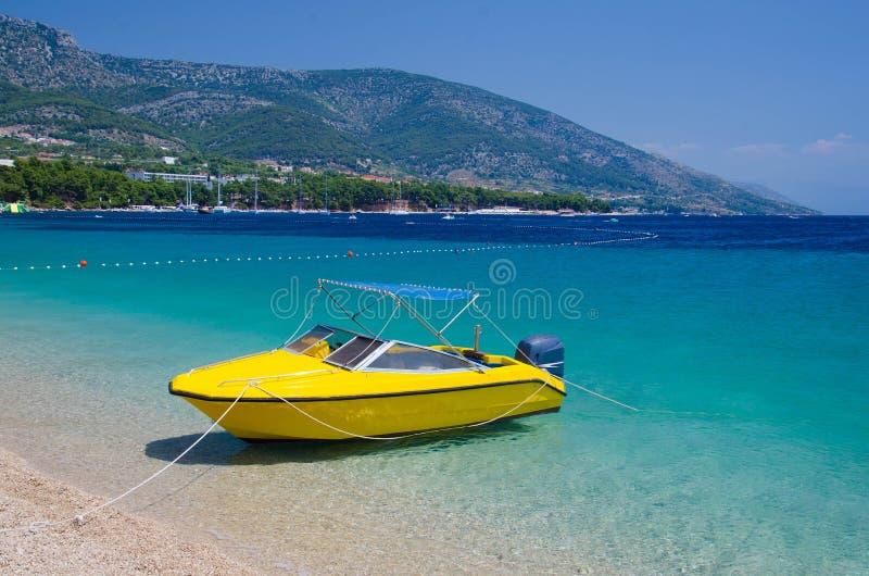 Barco amarillo cerca de la rata de Zlatni del cabo de la isla de Brac, mar adriático, C imagenes de archivo