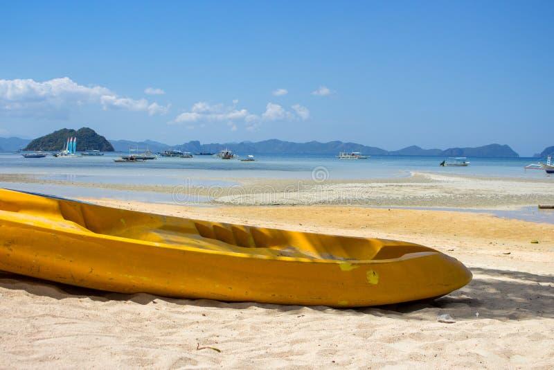 Barco amarillo en la playa de la isla en Filipinas Kajak en costa con las islas y los barcos tradicionales de Filipinas en fondo imagenes de archivo