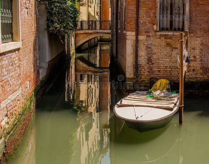 Barco amarrado perto de uma casa o na rua de Veneza fotografia de stock