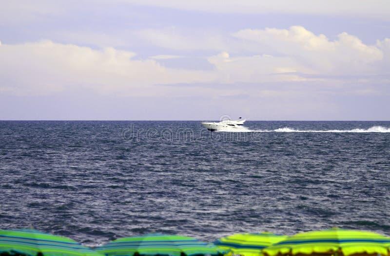 Barco aos guarda-chuvas do mar e de praia na praia imagens de stock