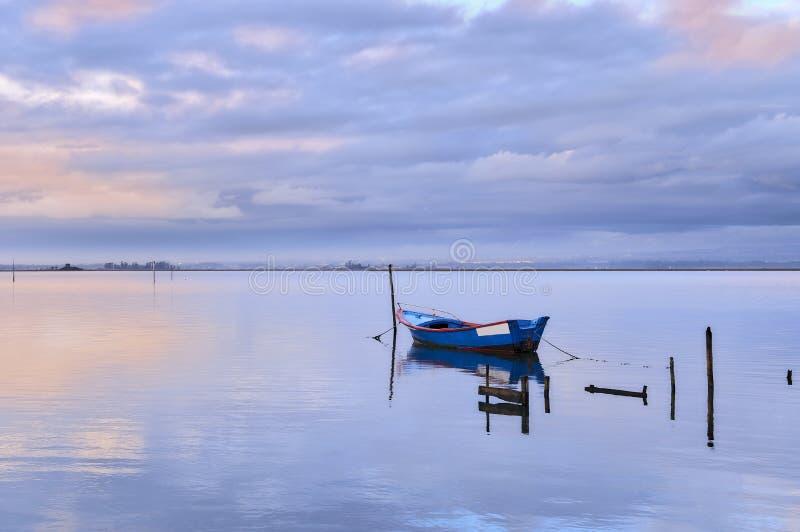 Barco azul apenas na lagoa no por do sol fotografia de stock royalty free