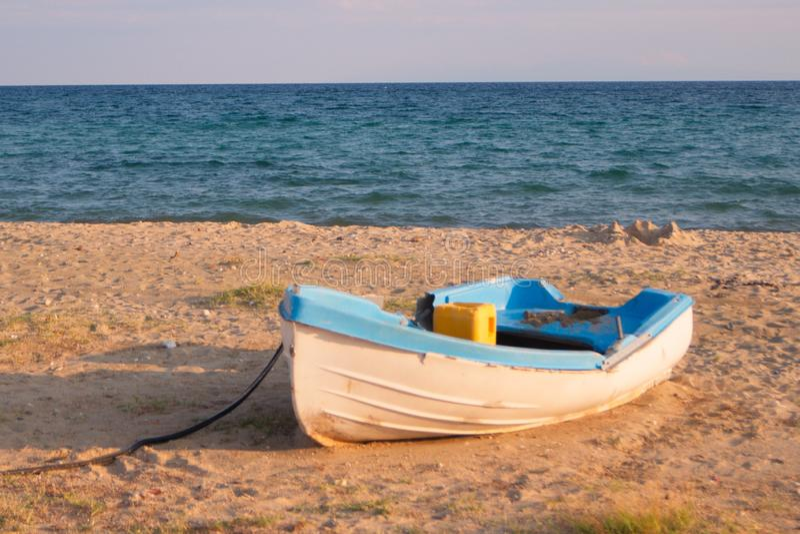 Barco azul blanco en una playa del verano imagenes de archivo