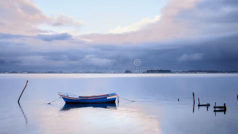 Barco azul com a luz do sol entre as nuvens foto de stock
