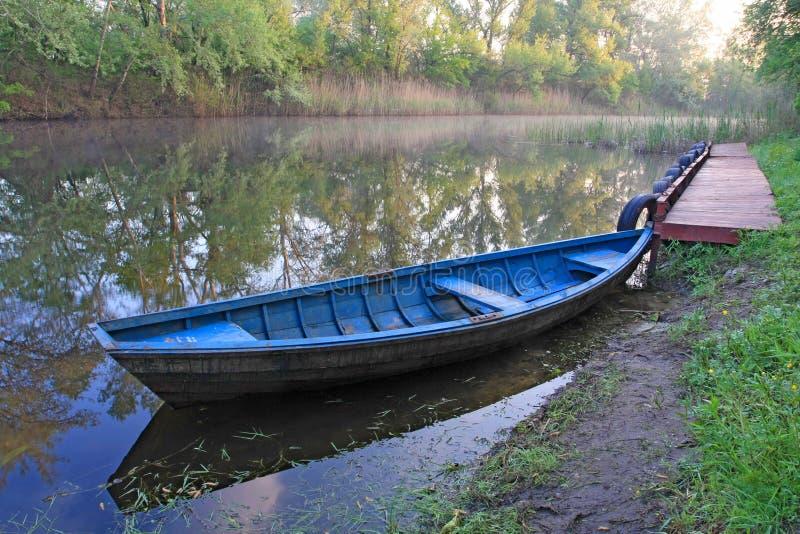 Barco azul en el río imagenes de archivo