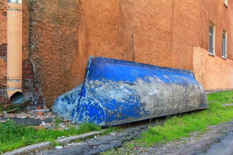 Barco azul invertido de pesca velho na grama verde no pátio da casa fotografia de stock