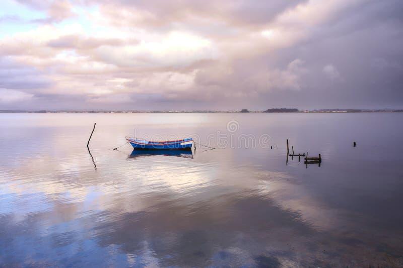 Barco azul no meio do lago sob o por do sol foto de stock