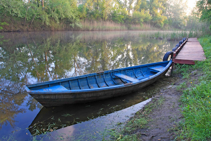 Barco azul no rio imagens de stock
