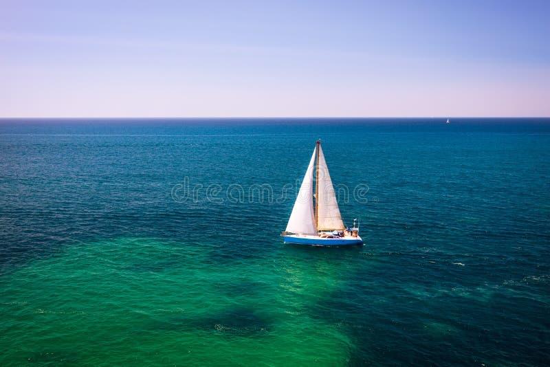 Barco blanco aislado en aguas azules. Velero en el mar a la luz del sol, lujosa aventura de verano, vacaciones activas en fotos de archivo